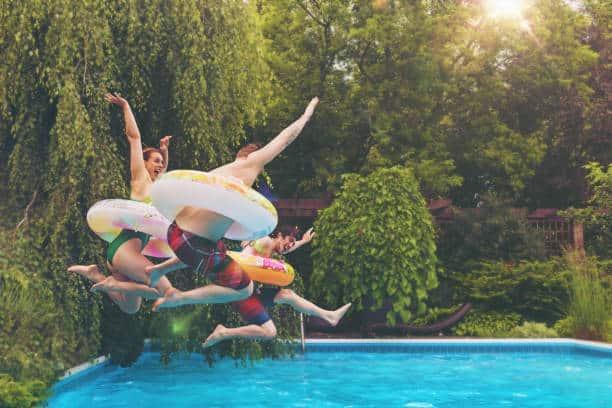 Famille qui saute dans sa piscine pendant les vacances à la maison